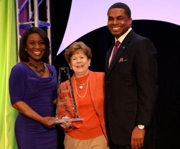 Jane McIntyre (center) stands with emcee Erica Bryant and Kieth Cockrell, Goodwill board member and Sr. Initiative Portfolio Executive, Bank of America